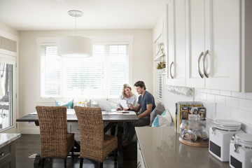 Couple paying bills, reading paperwork at laptop in breakfast nook