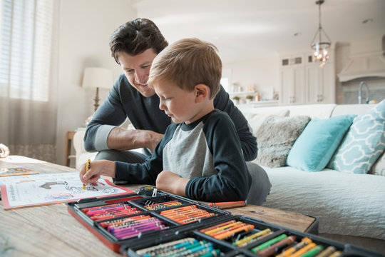 Father and son coloring in living room