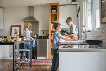 Family cooking and doing dishes in kitchen