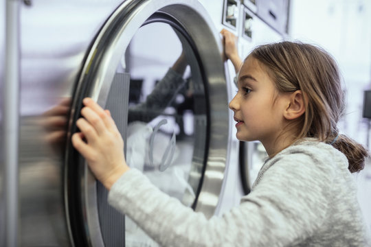 Curious girl watching laundry at dryer window in laundromat