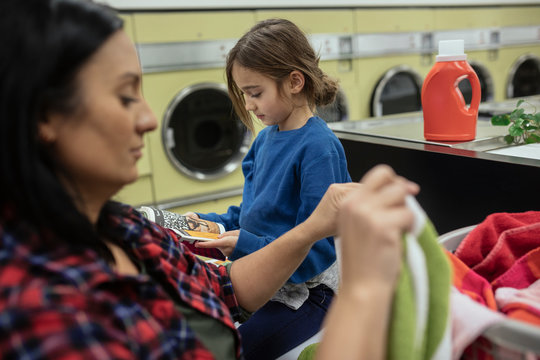 Mother and daughter doing laundry at laundromat