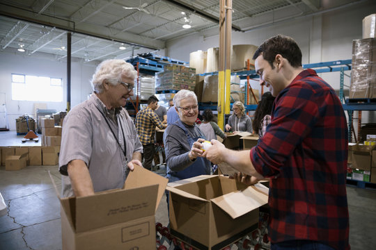 Volunteers filling donation boxes in warehouse
