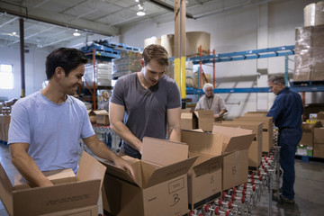 Male volunteers filling boxes for Food drive in warehouse