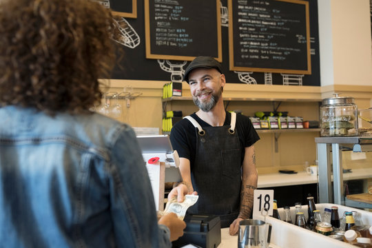 Friendly male barista taking money from female customer in cafe