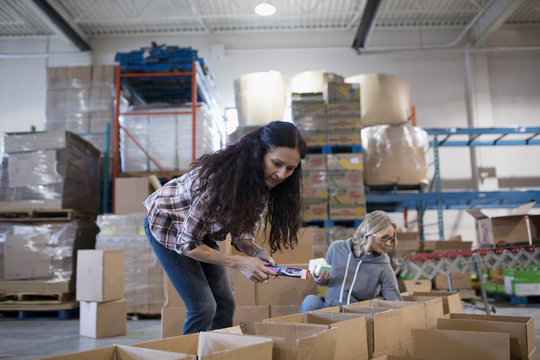 Female volunteers filling donation boxes in warehouse