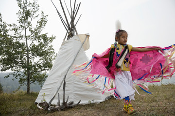 Native American Indian girl dancing in traditional clothing outside teepee