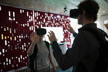 Computer programmers testing virtual reality simulator glasses