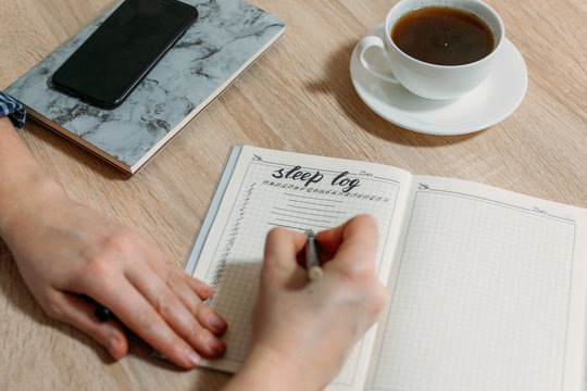 Woman hand with Sleep Log or Diary on table. How to Use a Sleeping Log to Diagnose Insomnia. Identify Sleep Disorders and Poor Sleep Habits