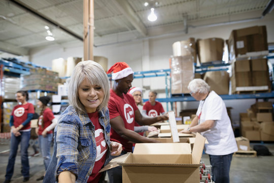 Female volunteer filling Christmas donation boxes in warehouse