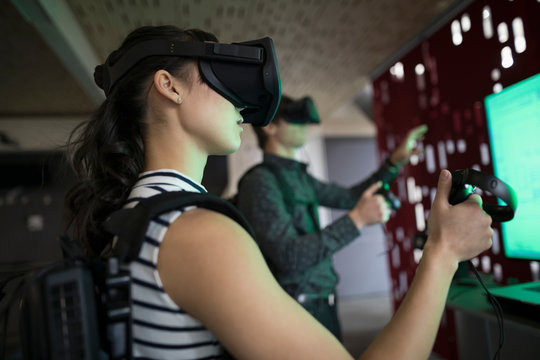 Computer programmers testing virtual reality simulator glasses and joysticks in office
