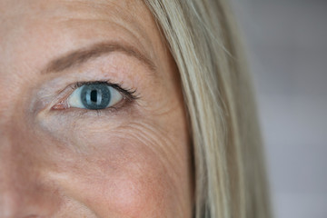 Close up confident mature woman with blue eyes and smile lines