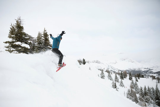 Exuberant man snowshoeing, jumping off snowy mountain hill