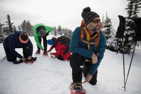 Smiling senior man putting on snowshoes with friends in snow