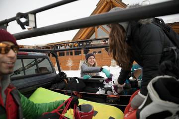 Friends unloading snowboarding equipment from truck at ski resort