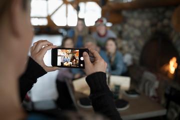 Woman photographing family skiers at ski resort lodge fireside apres-ski