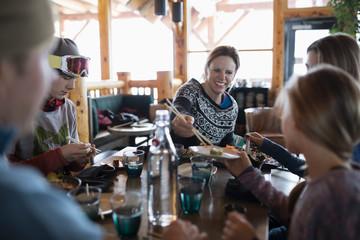 Family skiers enjoying sushi at ski resort restaurant apres-ski
