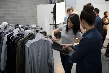 Wardrobe stylists browsing clothing on rack for photo shoot in studio