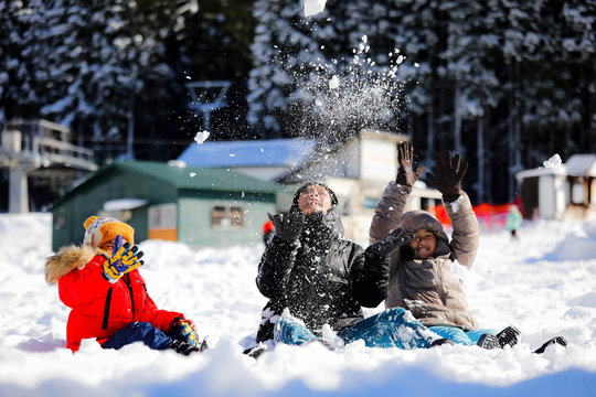 Asian girls playing snow happily in japan. ,  Children playing in the snow , Children playing in the snow happily.Asian boy playing snow happily in japan.