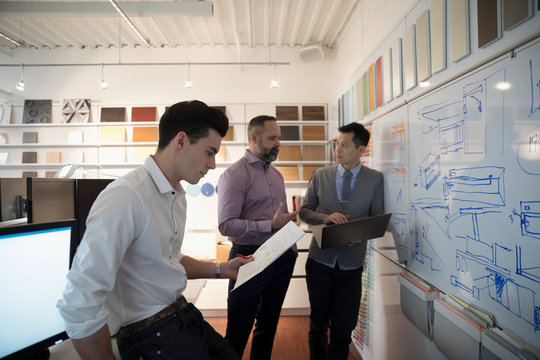 Designers with laptop brainstorming, meeting at whiteboard in creative office
