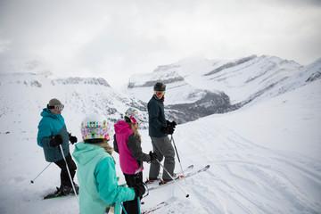 Family skiers skiing on snowy mountain