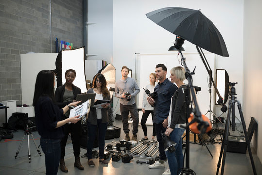 Photographers and production team meeting, preparing for photo shoot in studio