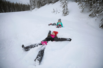 Playful girl making snow angel in snow