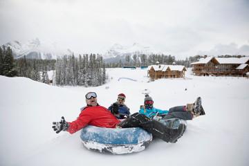 Portrait playful family inner tubing in snow at ski resort tube park Fotobehang
