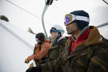Male snowboarder friends riding ski lift