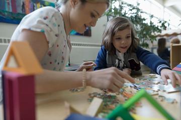 Preschool teacher and girl student assembling jigsaw puzzle