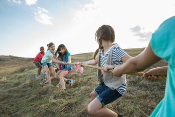 Schoolchildren playing tug-of-war on field