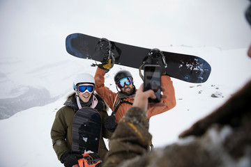 Man with camera phone photographing snowboarder friends in snow