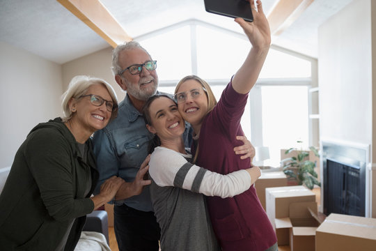 Parents helping affectionate lesbian couple move into new house, taking selfie