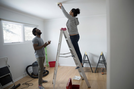 Young couple moving in, replacing light bulb with eco-friendly LED bulb, DIY