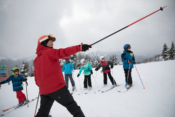 Kids receiving ski lesson from instructor on snowy mountain
