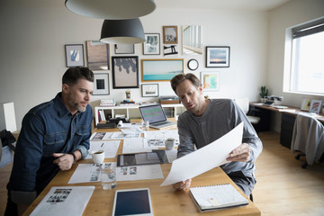 Male photo editors reviewing photo proofs in office meeting
