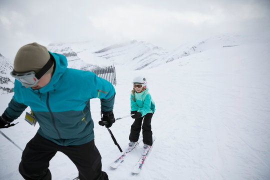 Father pulling daughter skier, skiing in snow