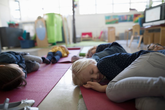 Tired preschool students sleeping on yoga mats during nap time