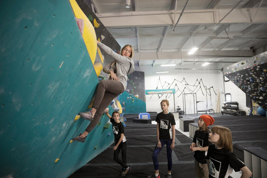 Girl rock climber students watching female instructor climbing wall at climbing gym