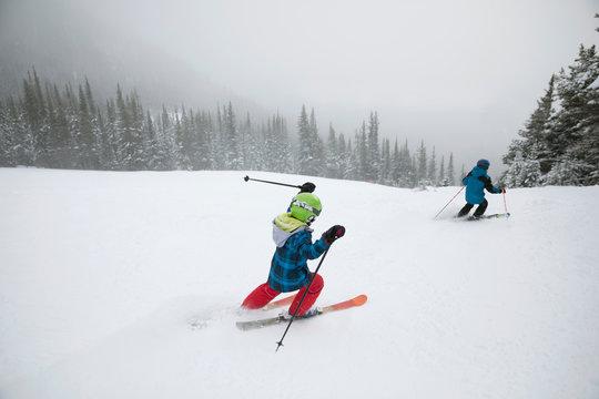 Boy skiing down snowy ski slope