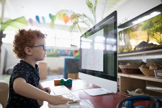 Focused preschool boy drawing at computer in classroom