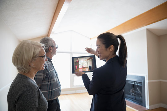 Interior designer with digital tablet showing senior couple augmented reality, planning living room remodel