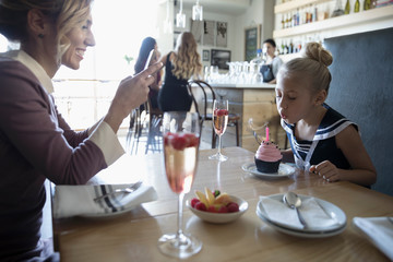 Mother with camera phone photographing daughter blowing out birthday candle on cupcake in cafe