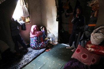 A displaced woman cooks at an unfinished apartment in Tripoli