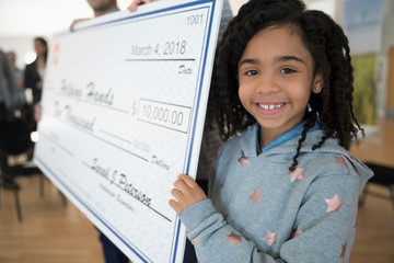 Portrait smiling, confident girl helping hold large donation check in community center