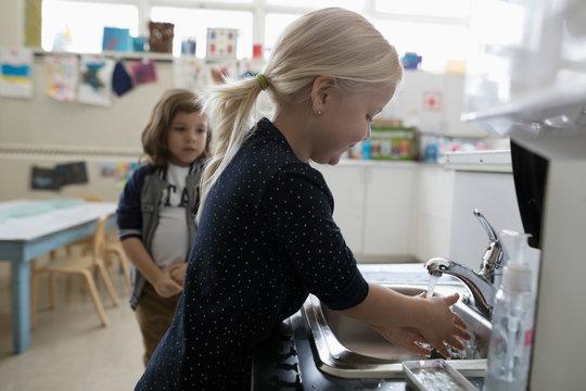 Preschool girl washing hands at sink in classroom