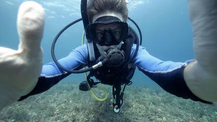 Underwater selfie photo of a male suba diver in the blue ocean.