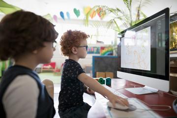 Preschool boy students drawing at computer in classroom