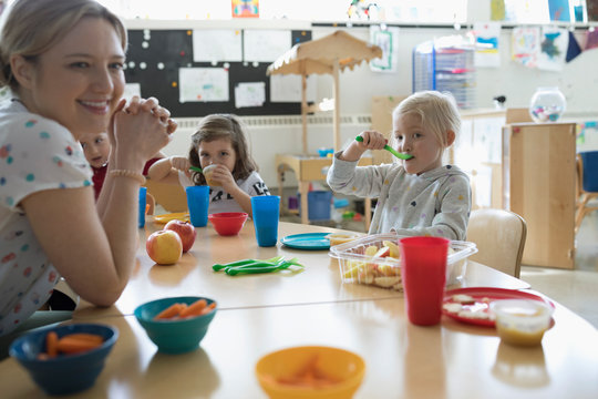 Preschool teacher and students eating during snack time in classroom
