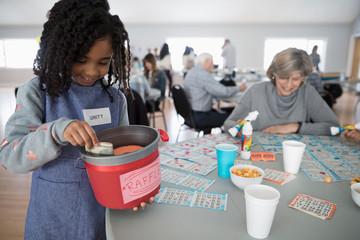 Girl selling fundraising raffle tickets at bingo in community center
