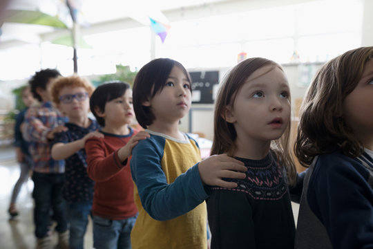 Focused preschool students lining up with hands on shoulders in classroom
